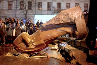 Protesters topple a statue of Soviet state founder Vladimir Lenin with a hawser during a rally organized by supporters of EU integration in Kiev