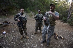 Together: Three Oath Keepers are seen armed Wednesday defending the mine
