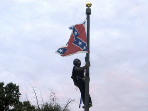Brittany Ann Byuarim Newsome climbed a flagpole to remove the Confederate battle flag at a monument in front of the State House in Columbia, S.C., on Saturday. Credit Bruce Smith/Associated Press