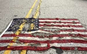 A partially burned American flag lies on the street near the spot where Michael Brown was killed  in Ferguson